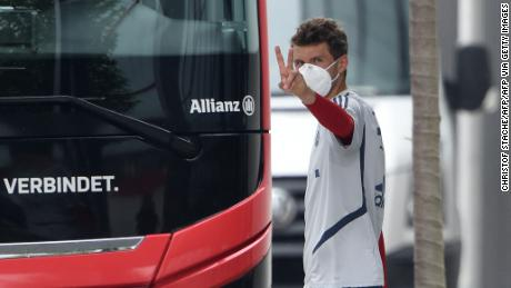 Bayern Munich forward Thomas Mueller wears a face mask as he leaves a training session.