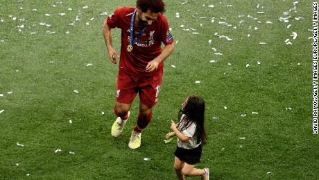Salah celebrates with her daughter Makka after her team's victory in the UEFA Champions League final.