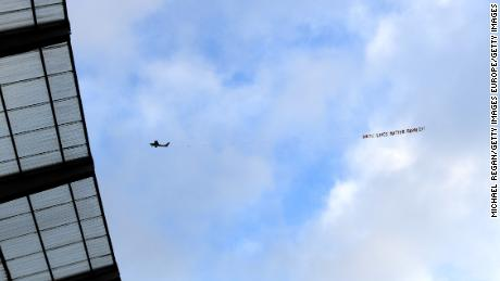 A plane flies over Etihad stadium with a banner