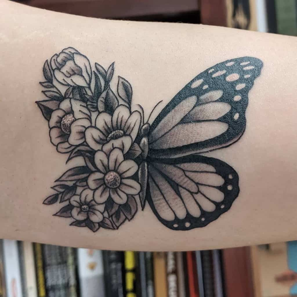 medium-sized black and grey tattoo on woman's upper arm of butterfly with one floral wing