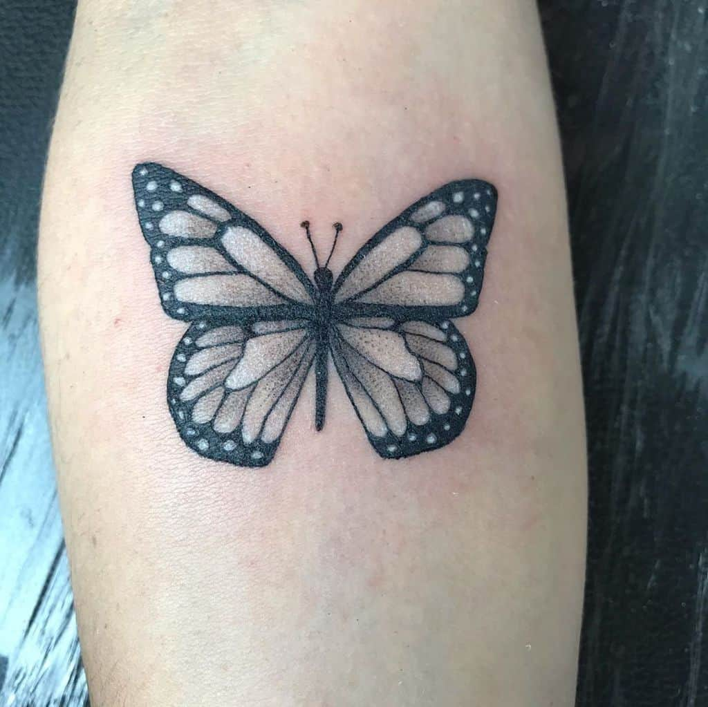 medium-sized black and grey tattoo on lower leg of a realistic butterfly with white highlights
