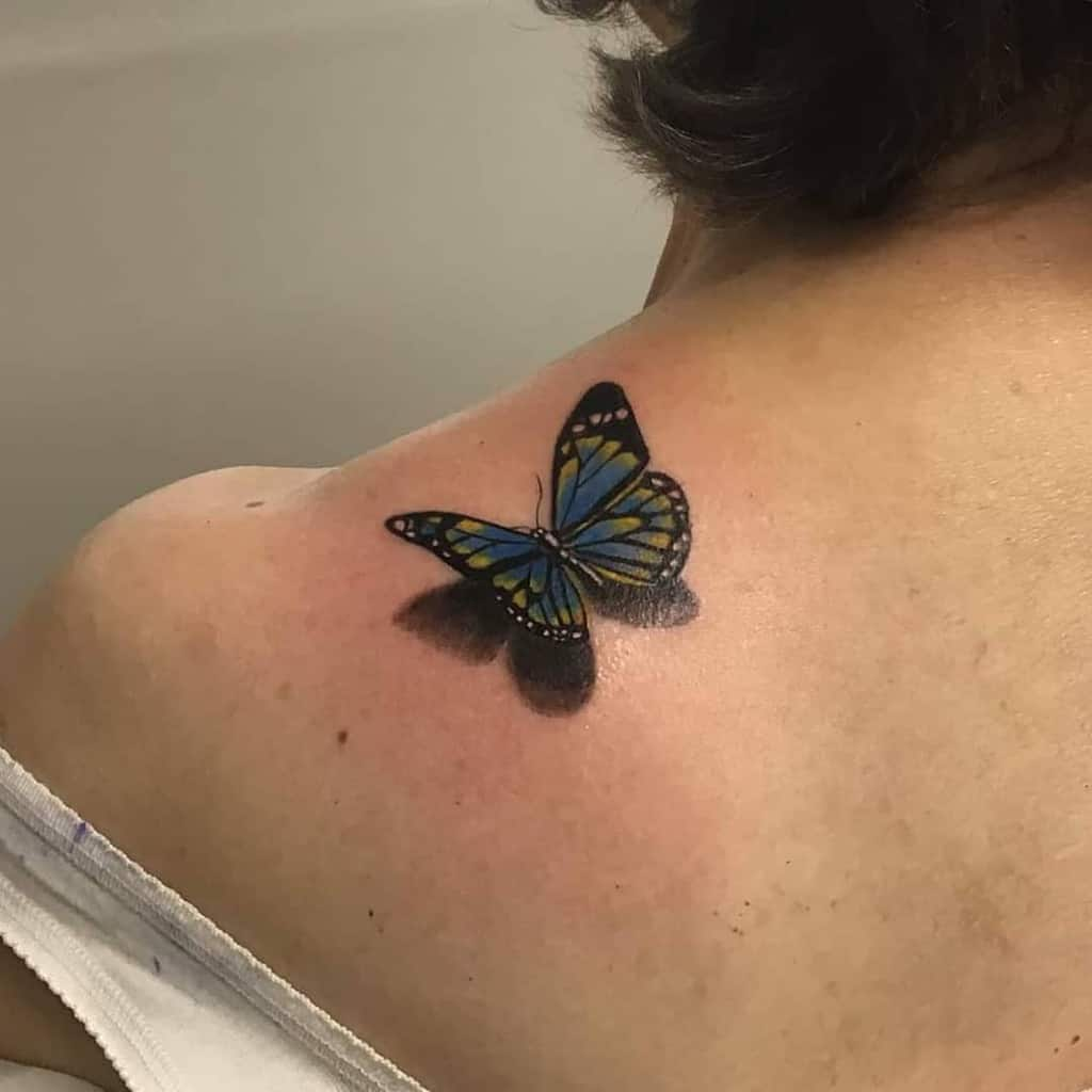 medium-sized color 3d tattoo on woman's shoulder of realistic blue butterfly with shadow