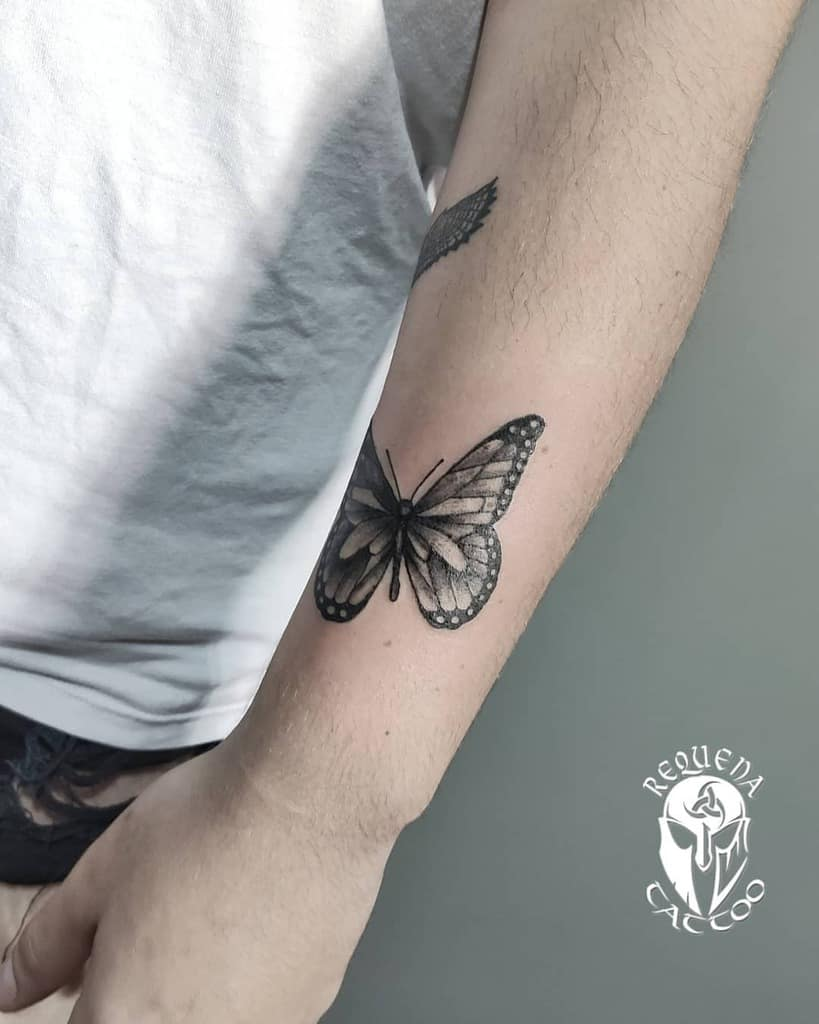 medium-sized black and grey tattoo on man's forearm of realistic butterfly