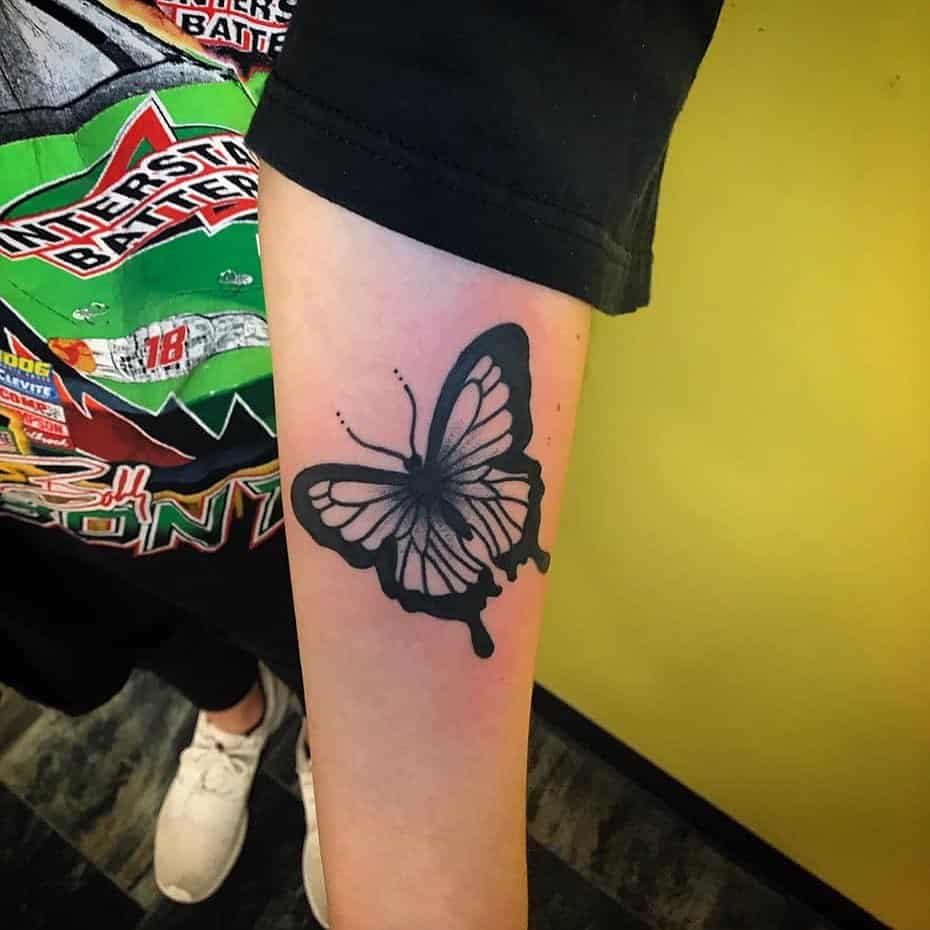 medium-sized black and grey tattoo on man's forearm of realistic butterfly with bold outline