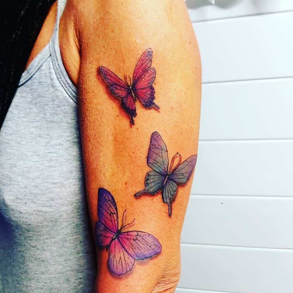 large color tattoos on woman's upper arm of three realistic pink and blue butterflies