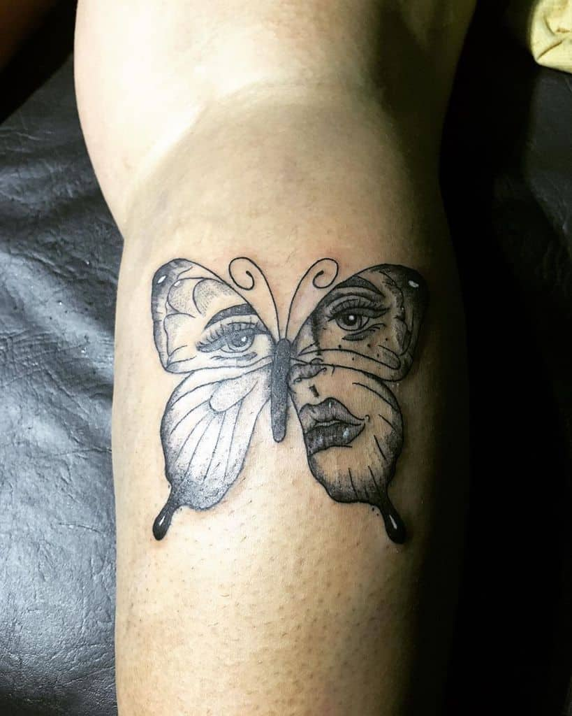 large black and grey tattoo on woman's lower leg of butterfly with woman's face inside wings