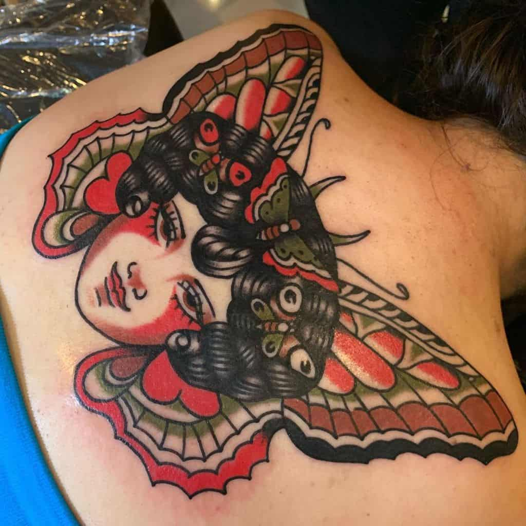 large color japanese tattoo on woman's upper back of a woman's face with butterflies in her hair and wings behind head