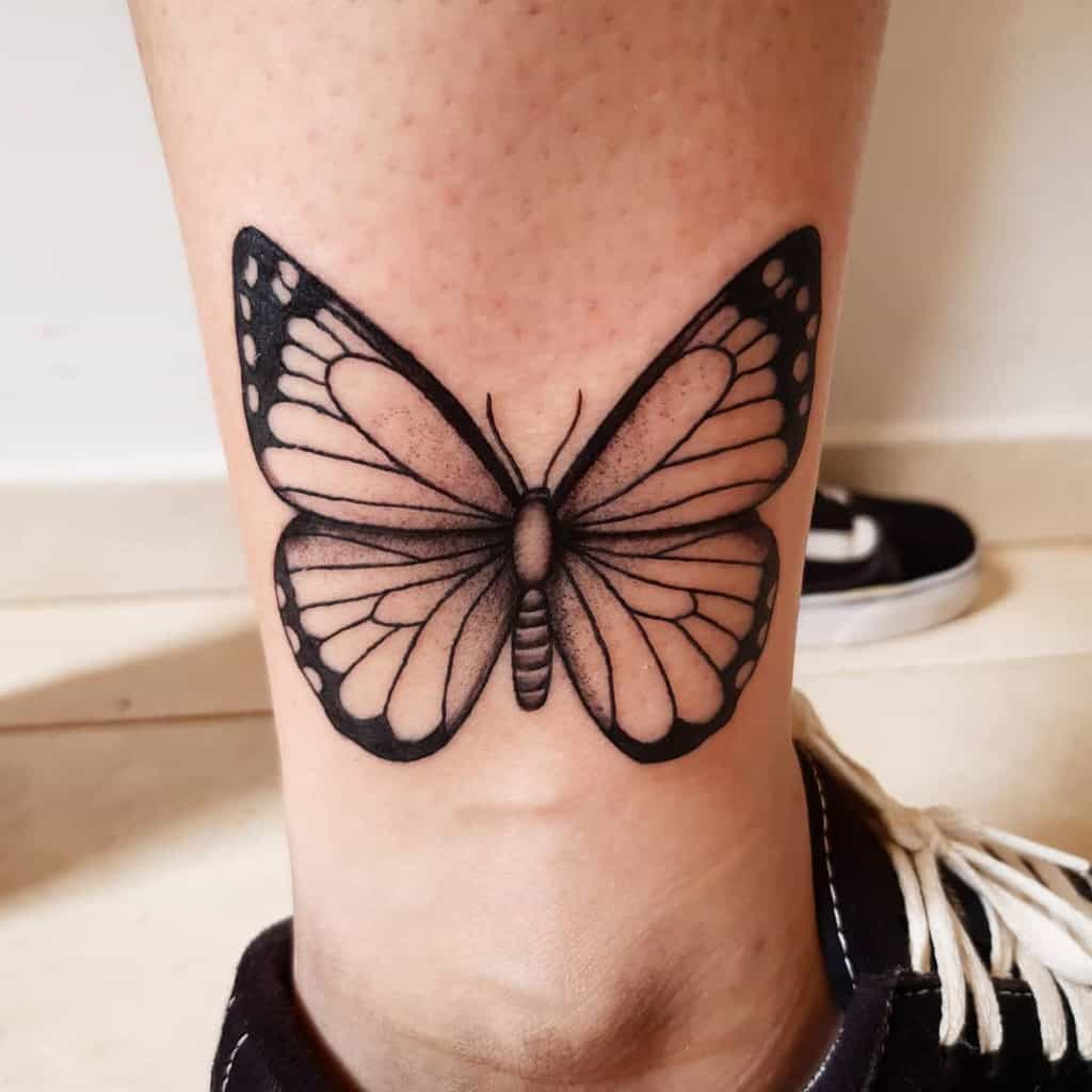 medium-sized black and grey tattoo on man's lower leg of realistic butterfly