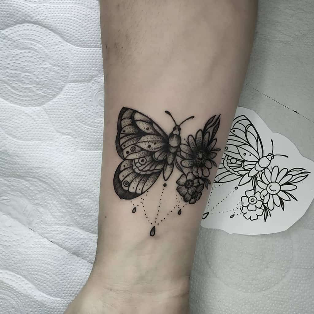 medium-sized black and grey tattoo on forearm near wrist of a surrealistic butterfly with one floral wing