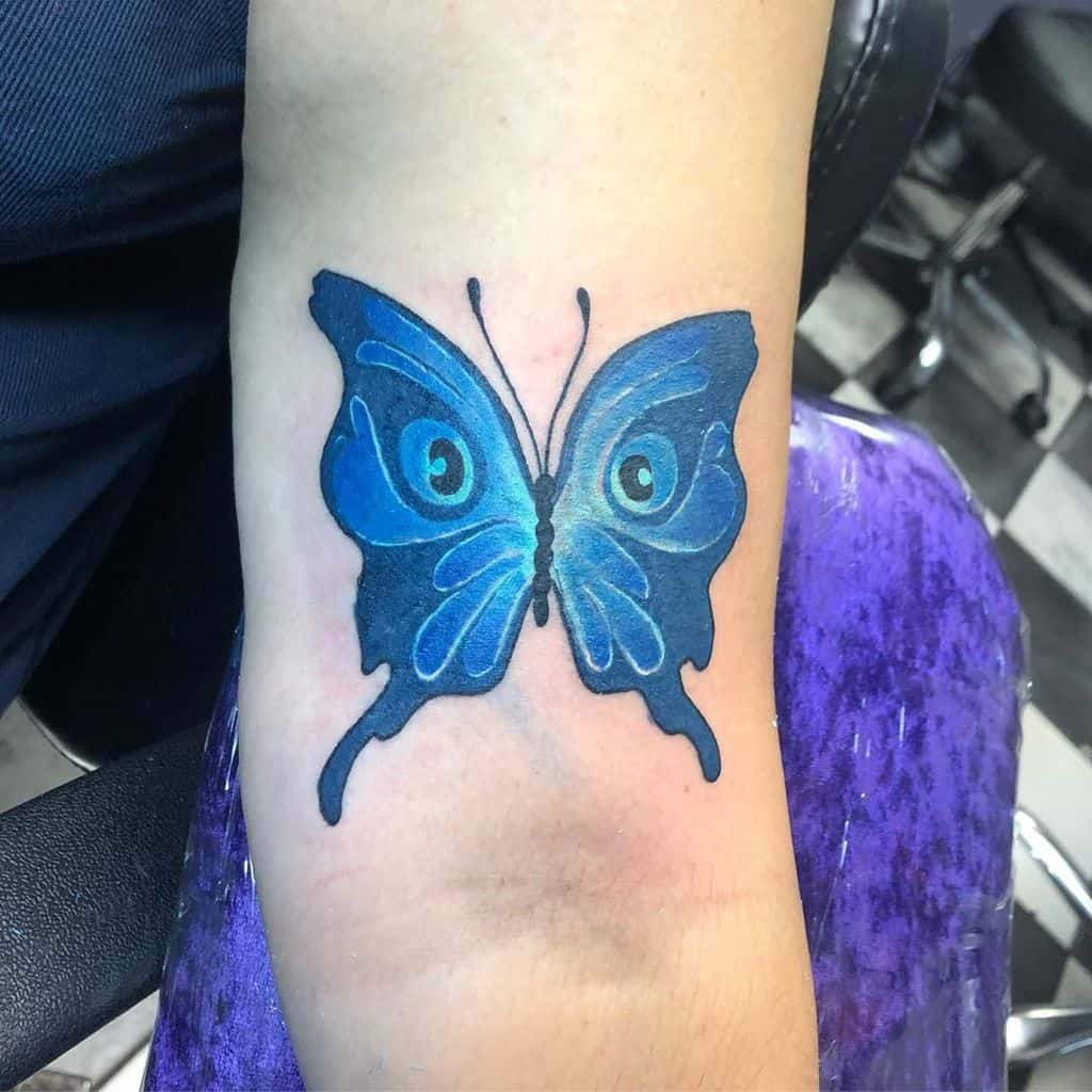 large color tattoo on woman's upper arm of blue butterfly with eyes on its wings
