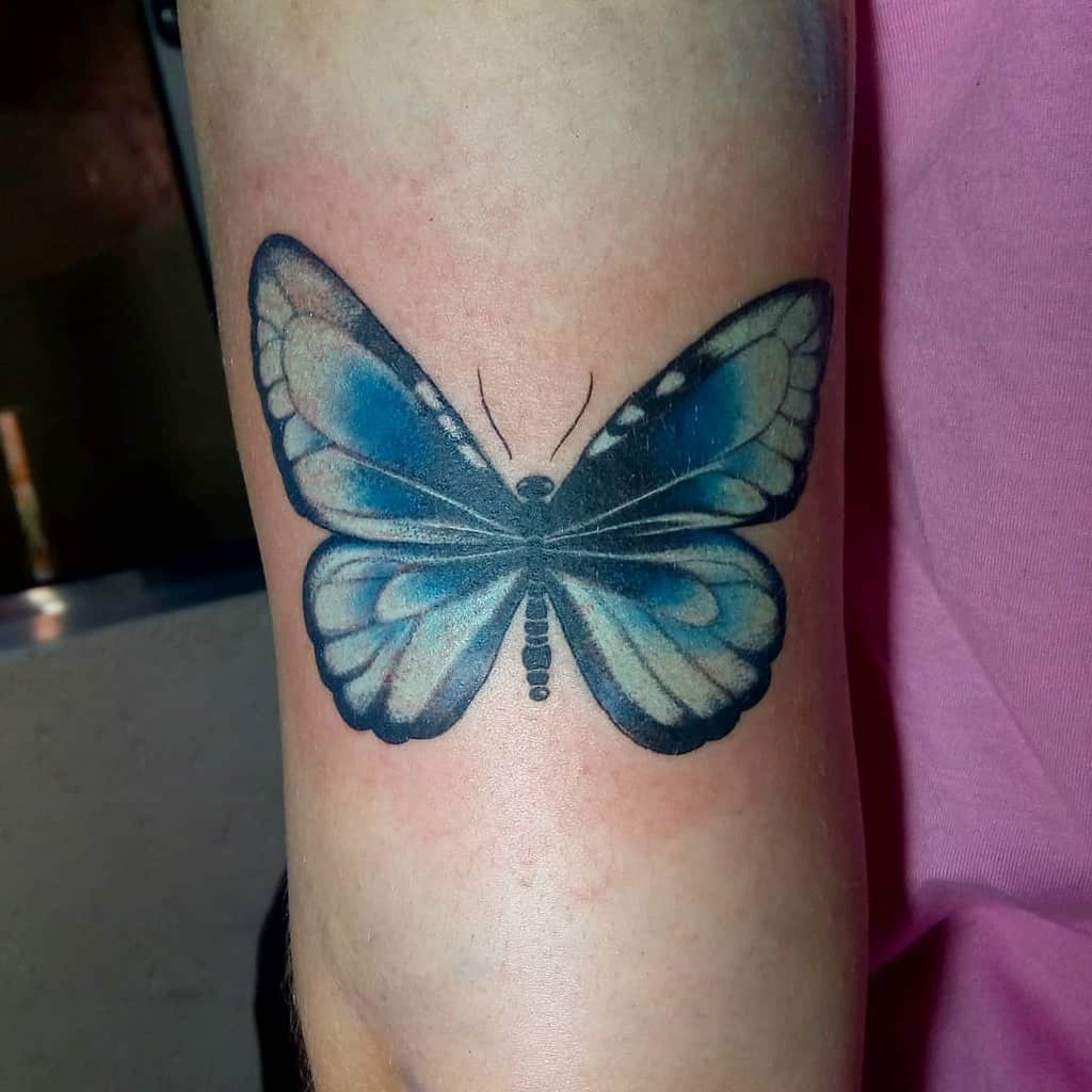 large color tattoo on woman's thigh of blue butterfly