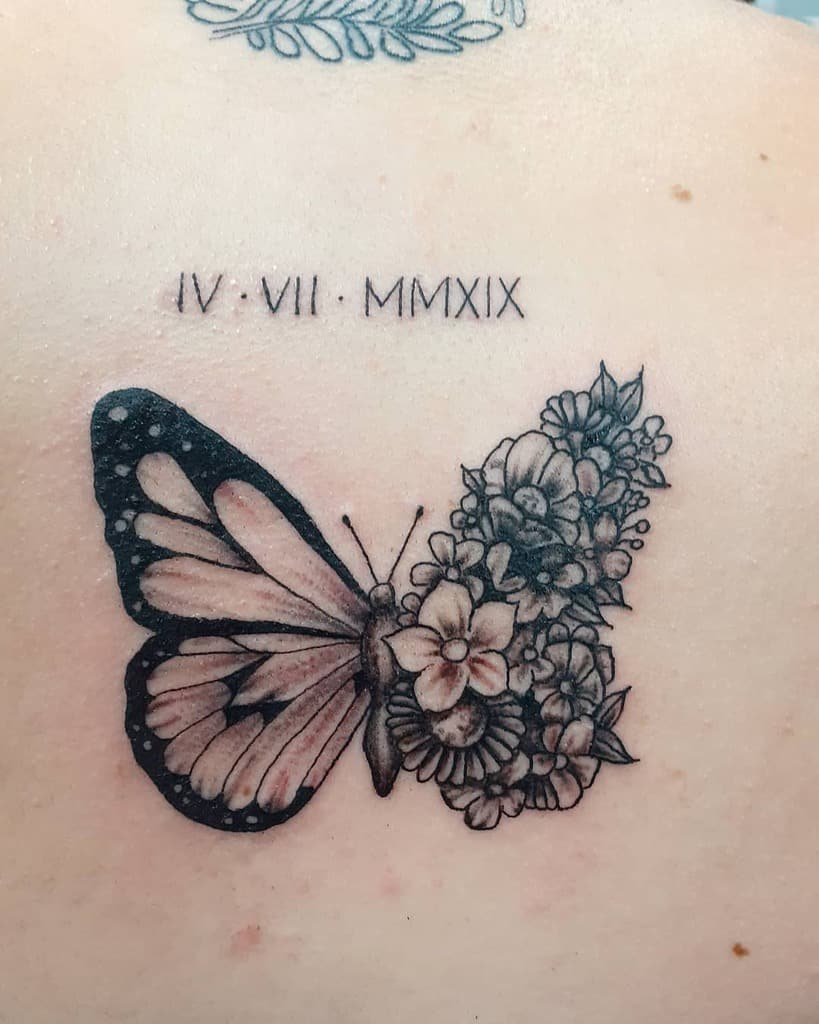 medium-sized black and grey tattoo on woman's upper back of butterfly with one floral wing