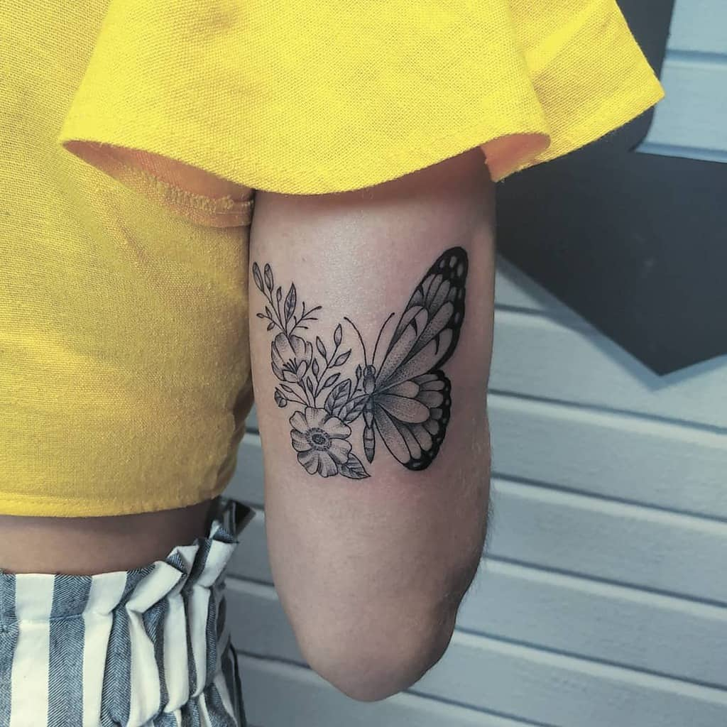 large black and grey tattoo on back of woman's upper arm of butterfly with one floral wing