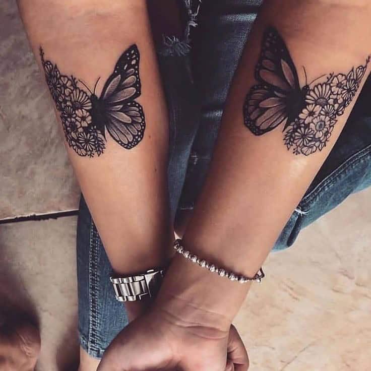 matching medium-sized black and grey tattoos on two women's forearms of butterflies with one floral wing