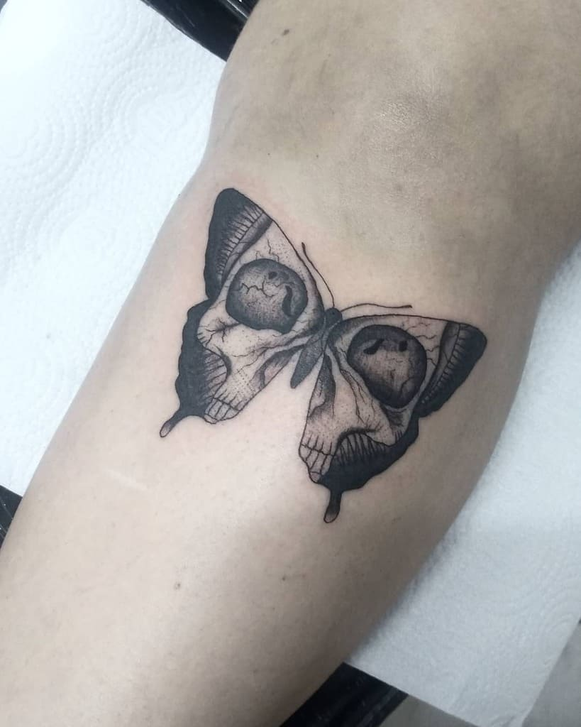 medium-sized black and grey tattoo on man's lower leg of a surrealistic butterfly with skull face in its wings