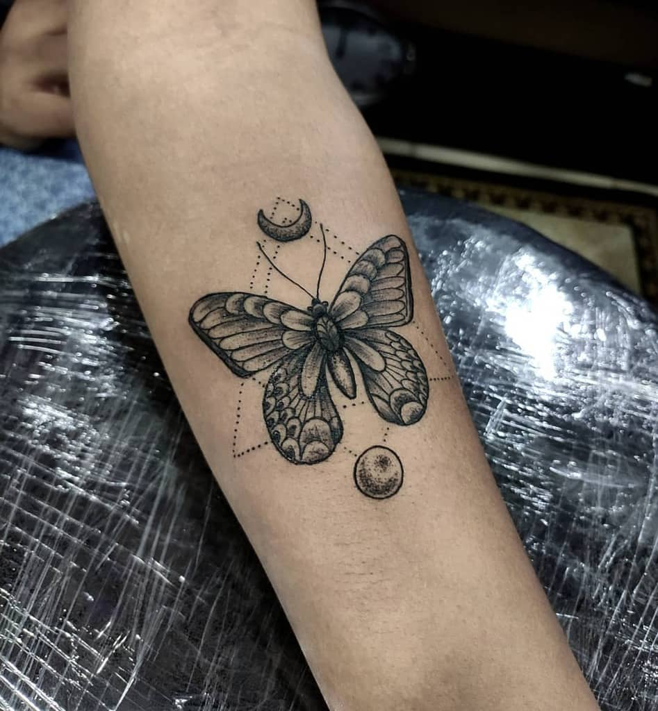 medium-sized black and grey geometrictattoo on forearm of a realistic butterfly inside dot triangle with crescent moon