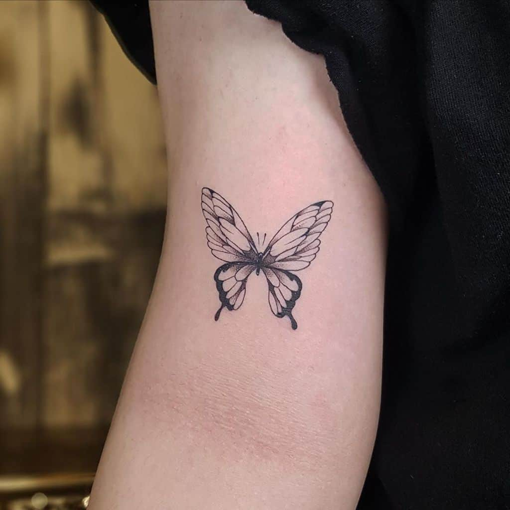 small black and grey tattoo on woman's upper arm of realistic delicate butterfly