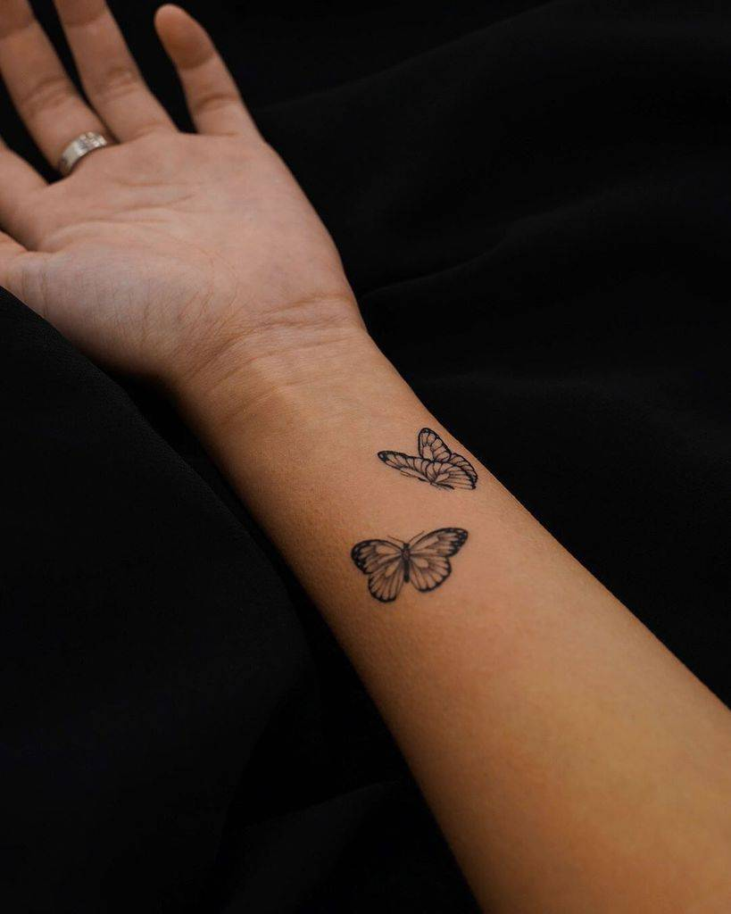 tiny black and grey tattoo on woman's inner forearm of two realistic butterflies