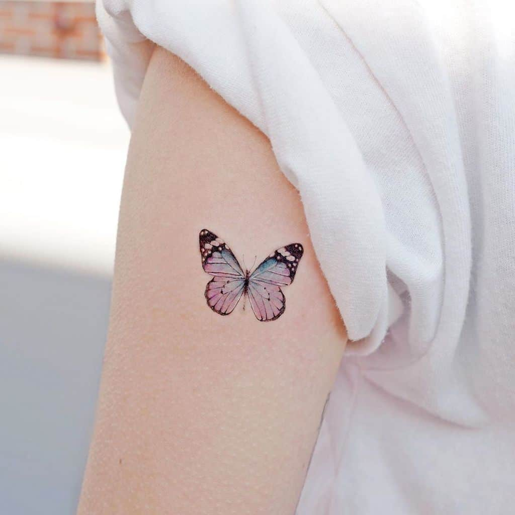 small color tattoo on woman's upper arm of a delicate pink and blue butterfly
