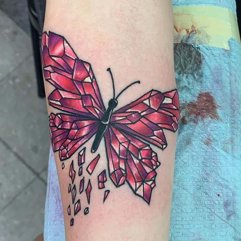large color geometric tattoo on lower leg of a surrealistic butterfly with wings made of pink crystals