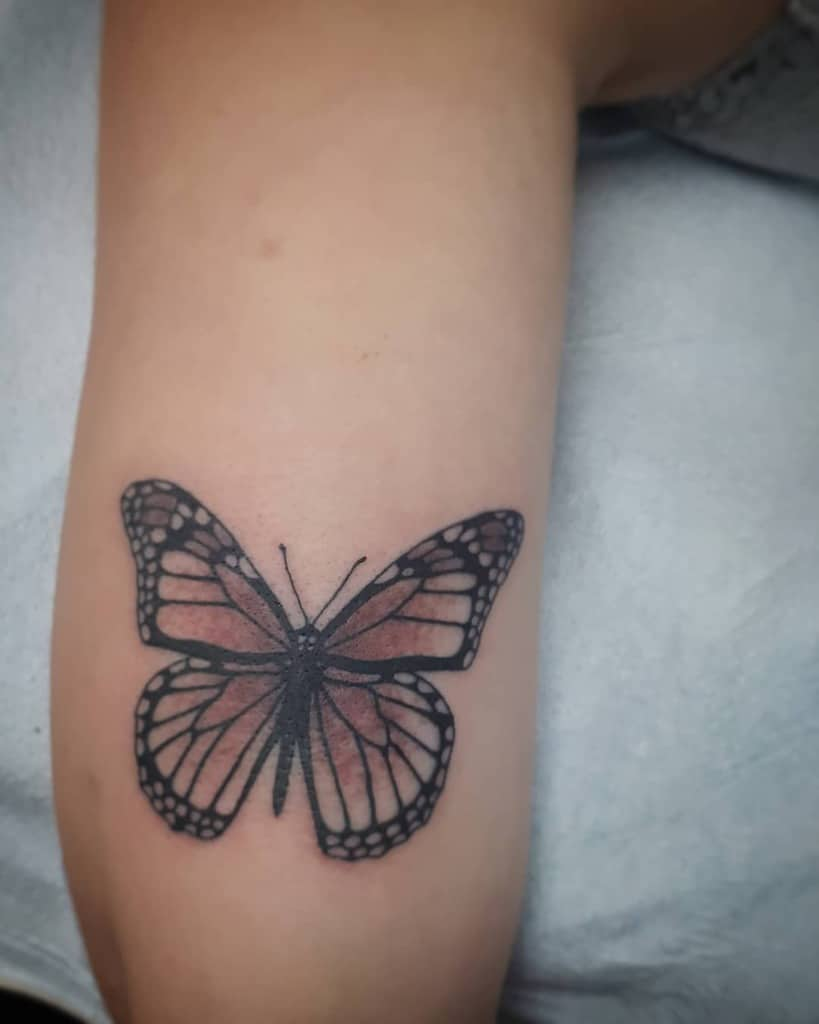 medium-sized color tattoo on woman's upper arm of a realistic brown butterfly