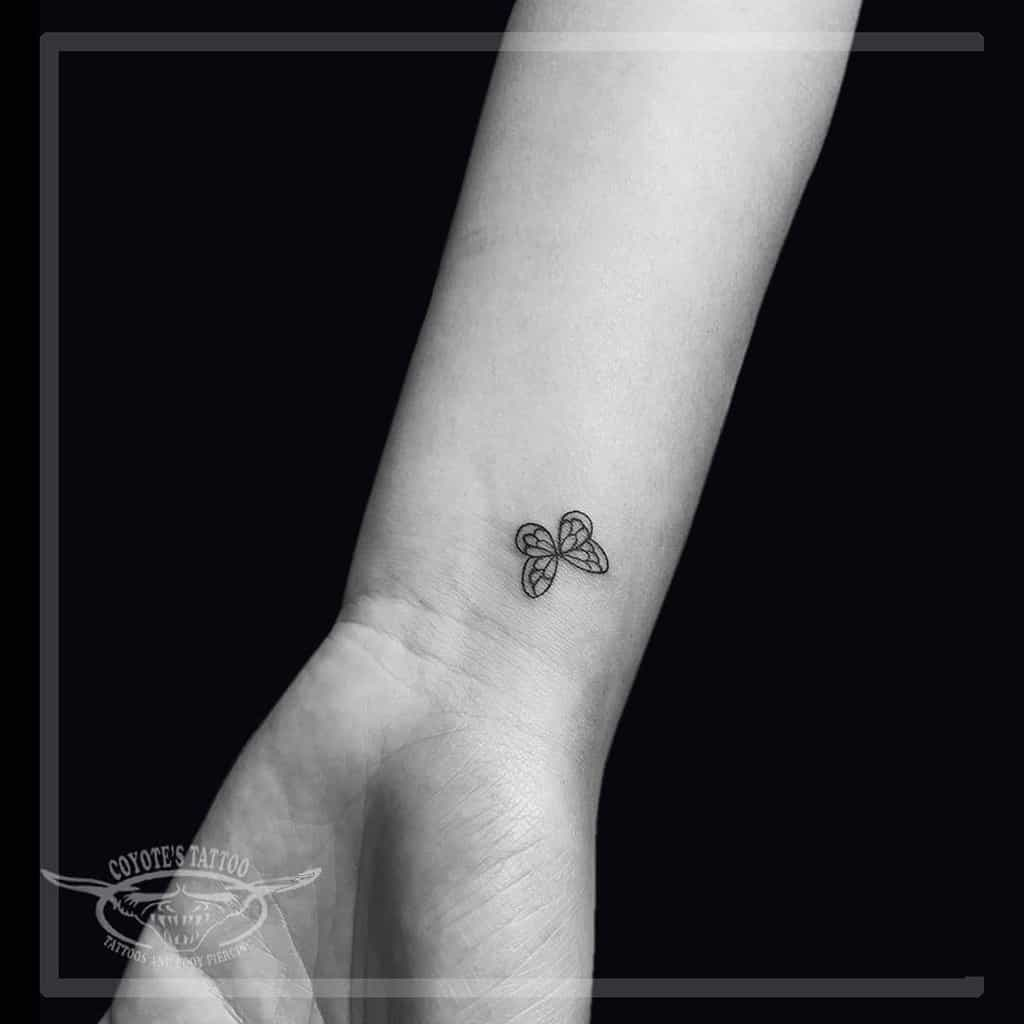 tiny black and grey line tattoo on woman's wrist of simple butterfly