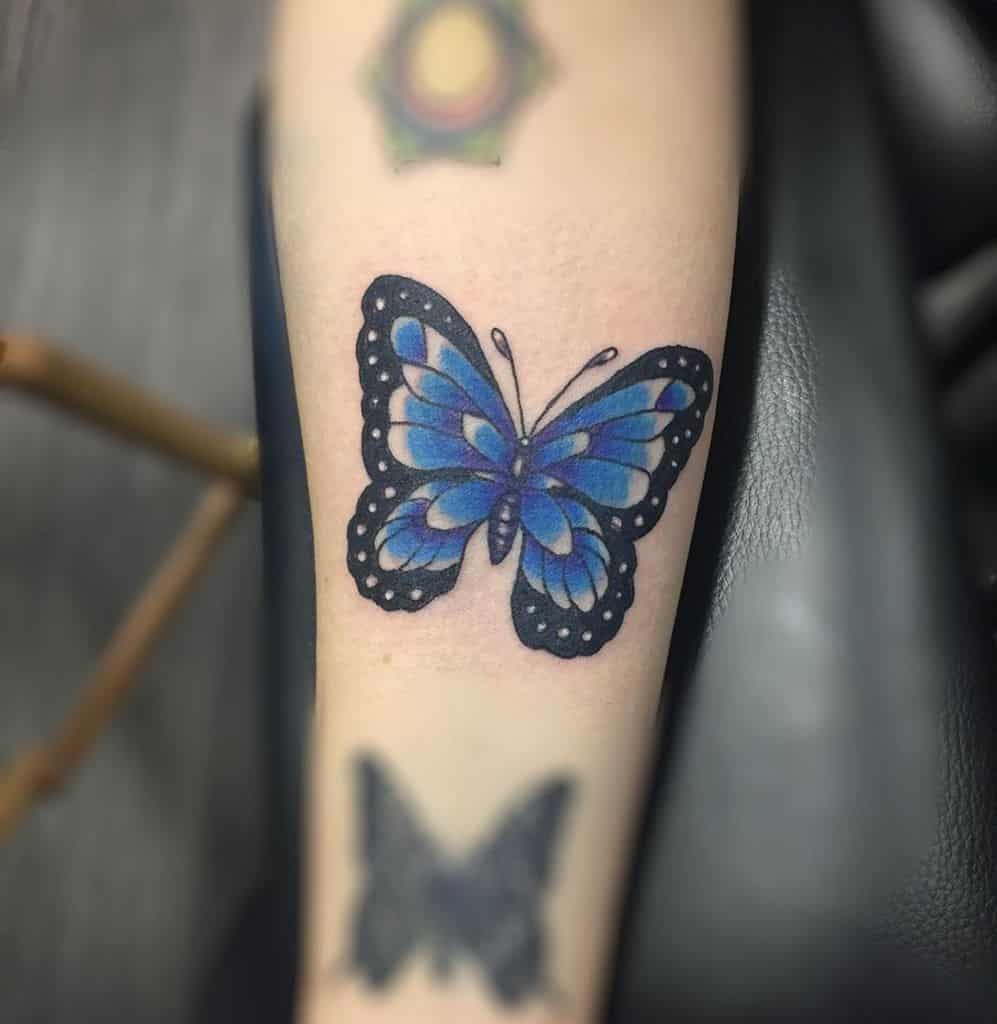 medium-sized color tattoo on woman's lower leg of blue butterfly