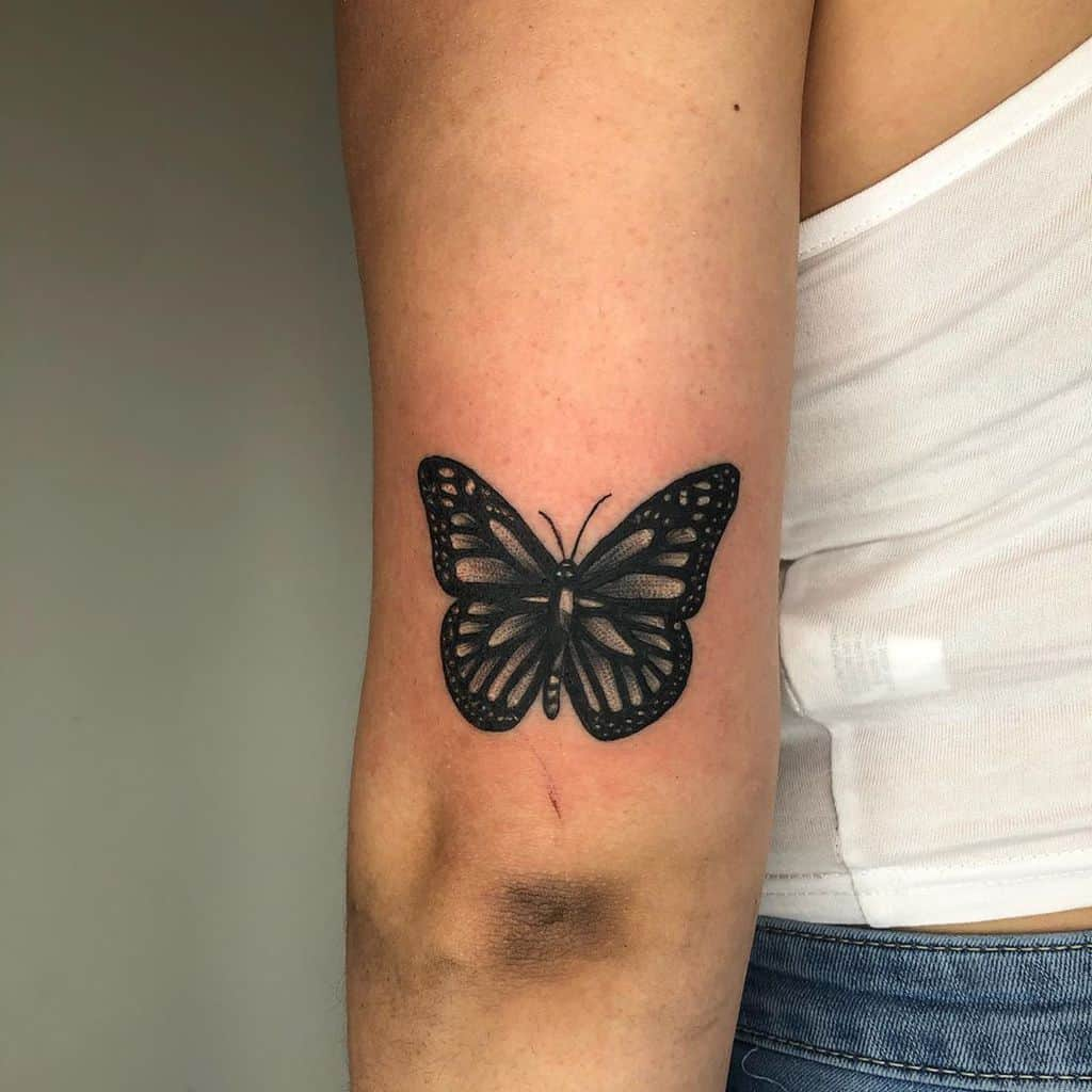 medium-sized black and grey tattoo on woman's upper arm of dark realistic butterfly