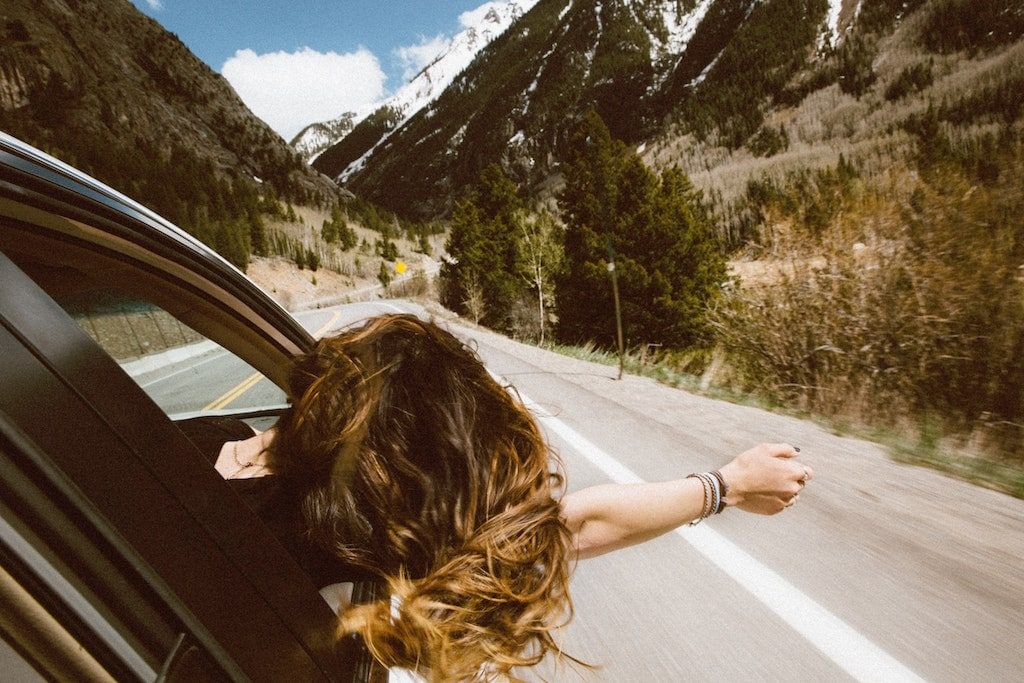 Woman with her head out the car window