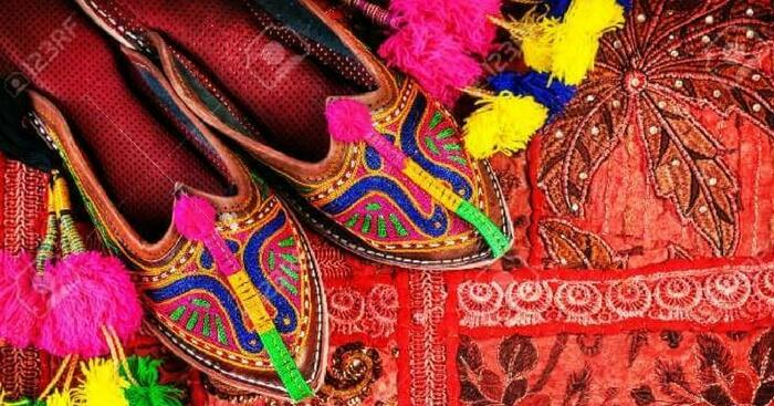 Traditional shoes on display with colorful backgrounds in Jaipur