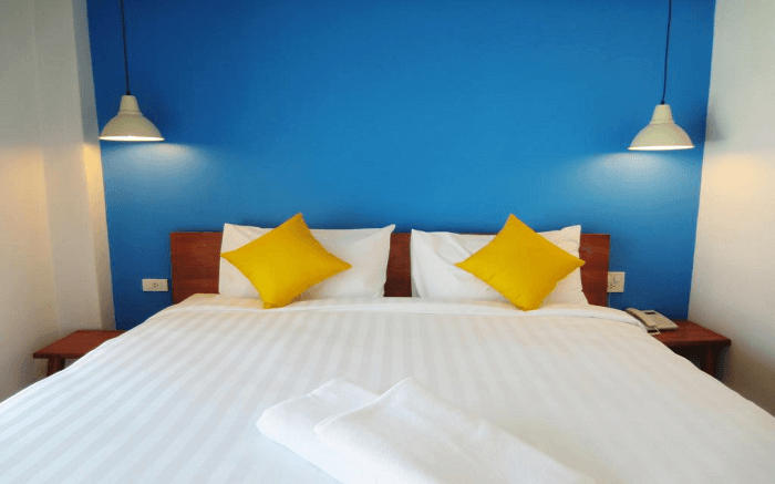Blue wall, yellow pillows in a room on the Sleep Whale Express