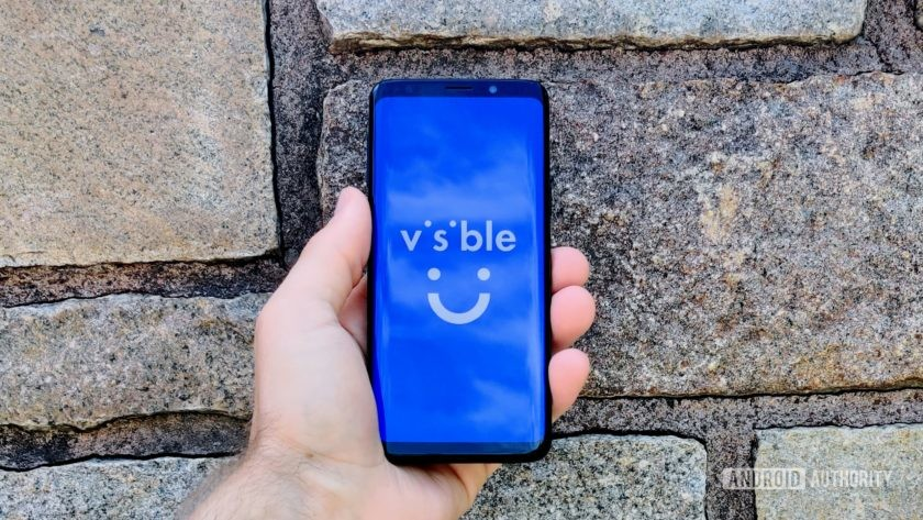 A Samsung Galaxy S9 in front of a wall with the Visible logo on the display.