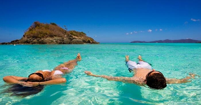 A couple floats in Caribbean waters in Trunk Bay, US Virgin Islands