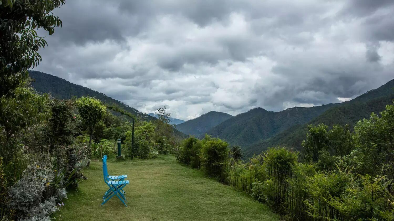 a bench in a garden overlooking the mountains