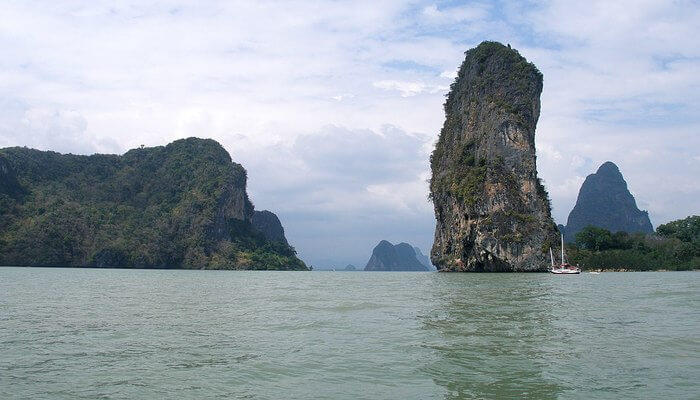 A couple relax in Phang Nga Bay on one of the best islands to go for a honeymoon in Thailand