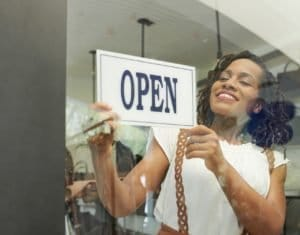 Cheerful woman opening store