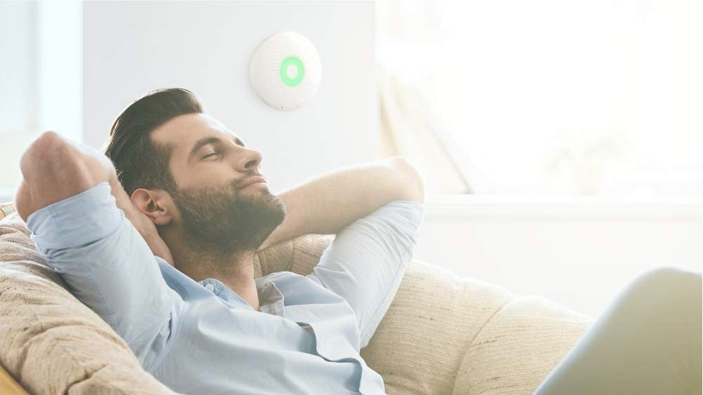 Lifestyle image of the Airthings Wave Plus next to peaceful homeowner