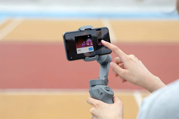 Person holding a DJI Osmo Mobile 3 gimbal while navigating on attached smartphone screen