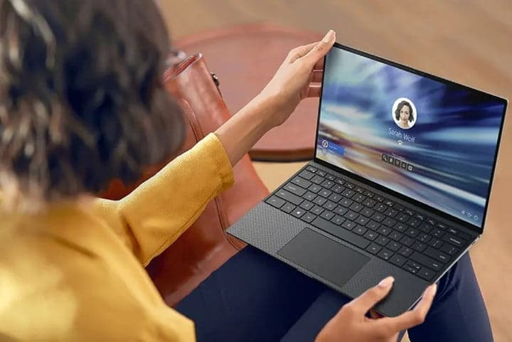 Person sitting and holding Dell XPS 13 laptop on their lap.