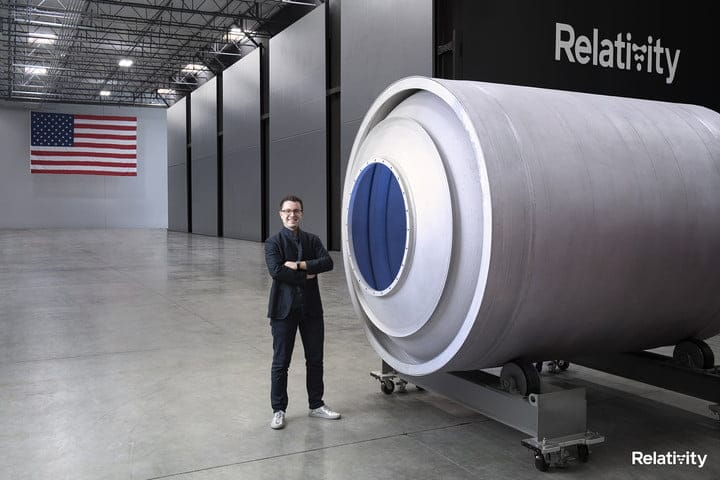 Relativity Space CEO, Tim Ellis standing next to a rocket component. An American flag is in the background.
