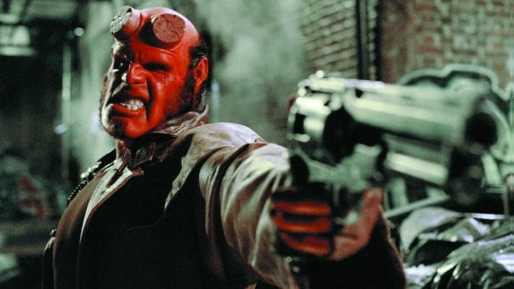 Hellboy gritting his teeth and aiming a gun at someone off-camera.