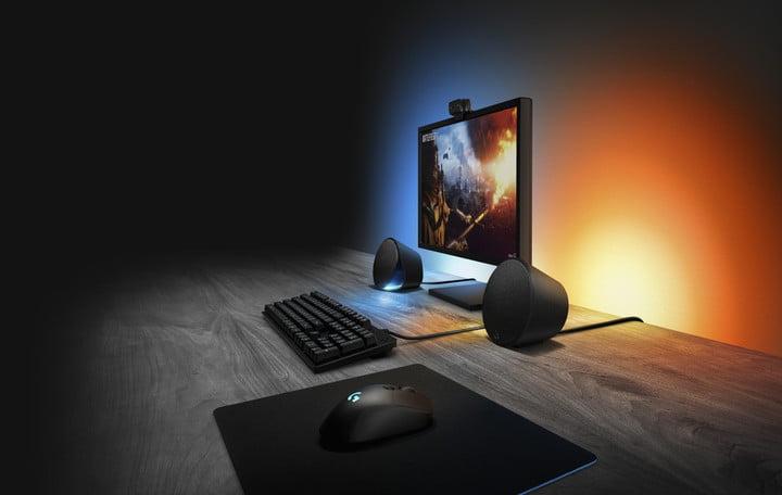 The Logitech G560 LightSync speakers on a desk beside a computer.