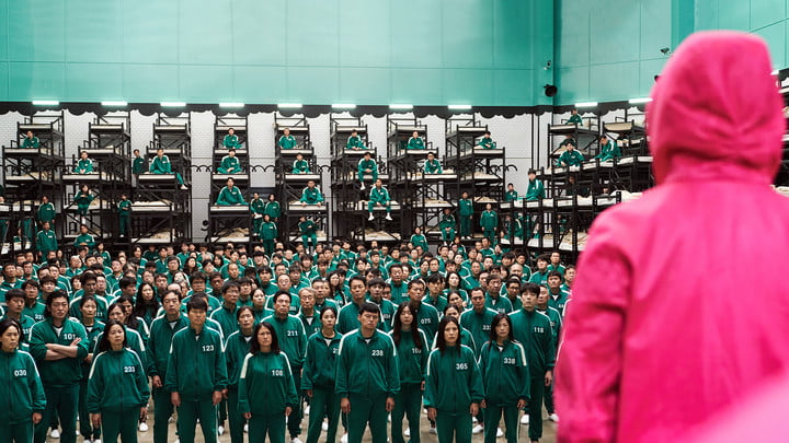 A worker in Squid Game standing in front of the many participants in numbered jumpsuits.